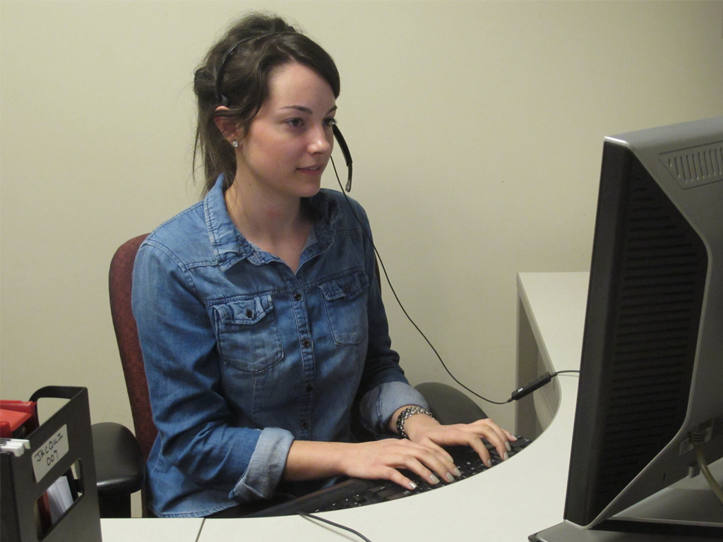 Woman working at a computer taking a call on a headset