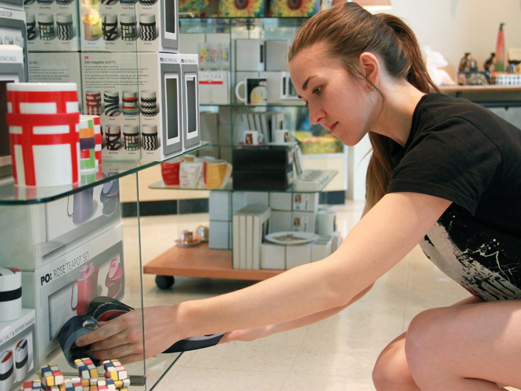 Woman adjusting a shelf display at a retail store