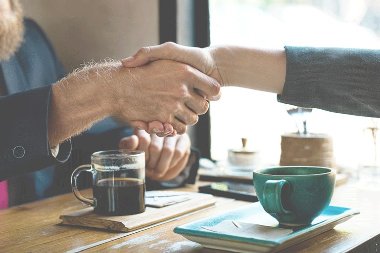 Two people meeting over coffee and shaking hands